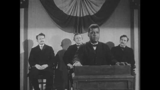 1950s: Man speaking at podium, zoom in on man.