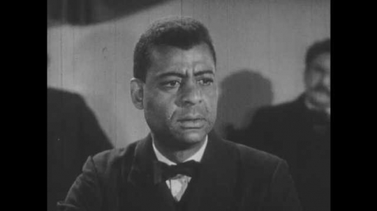 1950s: Close up of man speaking. Man shakes hands with crowd, zoom out. Man enters room, talks to man at desk.