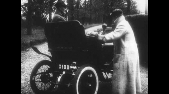 1950s: UNITED STATES: man starts early motor car. Motor car with engine. Car drives along road. Men in car