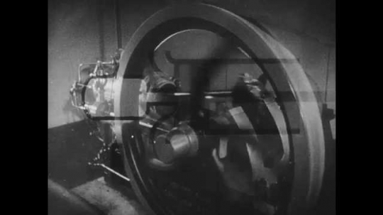 1950s: UNITED STATES: fly wheel turns on machine. Close up of running engine. Hornsby engine. Heat engine at work.