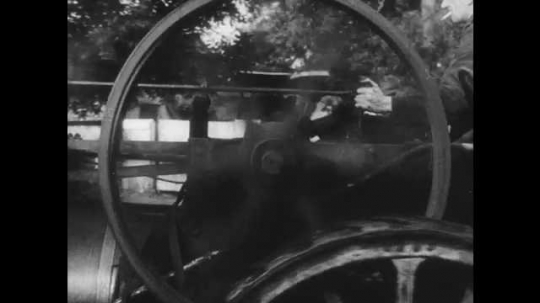 1950s: UNITED STATES: men drive steam engine. Gasoline engine drives motor car. Flames flicker