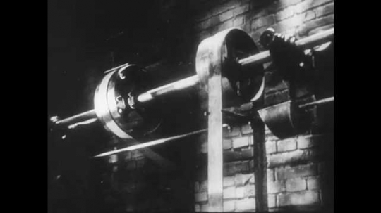 1950s: UNITED STATES: engine turns in room. Men operate experimental machine. Fly wheel on machine
