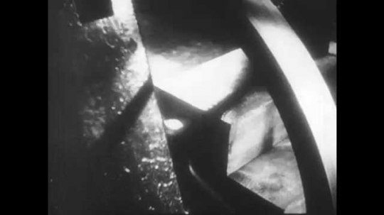 1950s: UNITED STATES: fly wheel on working machine. Close up of machine piston. Men watch experimental machine engine