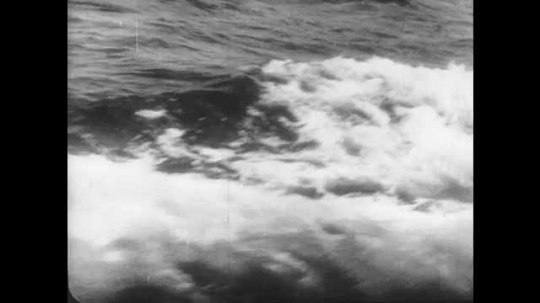 1950s: UNITED STATES: wake behind ship. Submarine at sea. Water around submarine