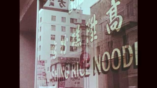 1970s: Front window of Chinese restaurant. A clown performs on the street. Trio of violinists perform on the street. Cable car goes up the street. Passenger view of the street from the cable car.