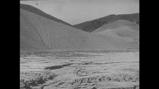 1940s: UNITED STATES: man walks across field after rain. Water erosion in field. Man and woman walk across fields