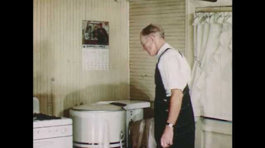 1950s: Man standing at stove, pours himself cup of coffee and drinks it.