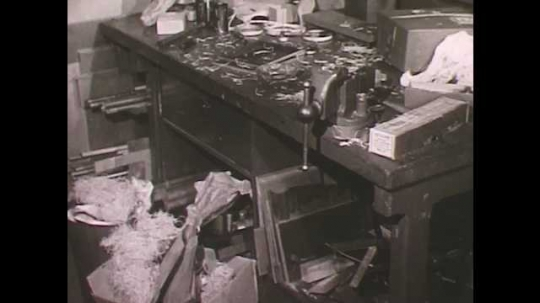 1950s: Workshop full of rubbish.  Trash disappears.  Rag unfolded.  Man puts rags in metal trash can.  Woman in lab pours liquid.