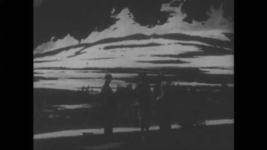 1940s: People standing in front of mountain, tilt up to mountain. View of mountain and lake. Close up of waterfall. View of mountains. Tracking shot of car on road.