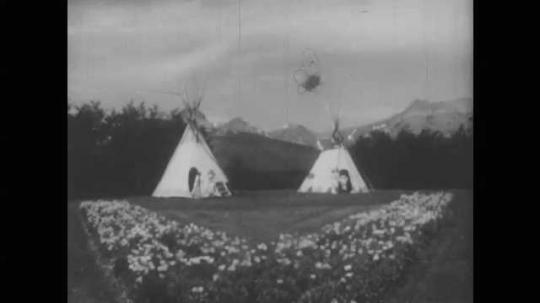 1940s: Long shot, people exit teepee. People sit on ground. People in costume talking.