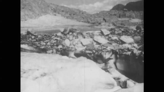 1940s: Long panning shot of glaciers. Pan from mountain to lake.