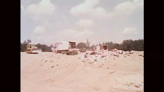 1970s: UNITED STATES: Refuse truck empties waste into landfill site. Waste from lorry.