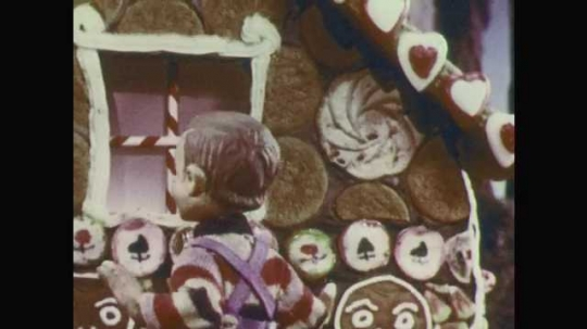 1950s: Stop-motion animation.  Boy and girl take pieces of gingerbread house.  Witch opens door.  Children turn in surprise.  Girl hides behind boy.  Witch walks out.  Children look at each other.