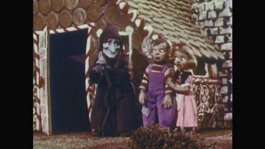 1950s: Stop-motion animation.  Witch stands with children.  Witch pats boy's head.  Witch gestures inside gingerbread house.  Boys smiles and walks in.  Girl and witch go in house.  Door closes.