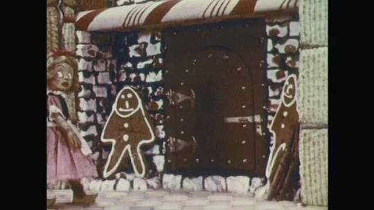 1950s: Stop-motion animation.  Girl picks up firewood and throws in oven.  Witch walks over and grabs girl.  Girl shakes her head.  Witch pushes girl.