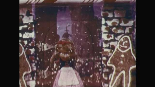 1950s: Stop-motion animation.  Gingerbread house disappears around girl.  Cage disappears setting boy free.  Children hug and spin.  Children look around.  Rabbit hops on trail.