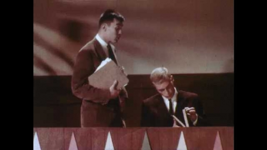 1950s: UNITED STATES: two men talk on television set. Man looks at papers. Man in library. Men look for book on shelf
