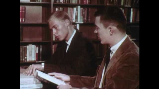 1950s: UNITED STATES: two boys look through books in library. Trends in automation title in book. Copyright date in book. Hands close book. Hands open book