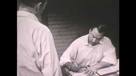 1960s: Man at table writes, hands paper to other man, walks across room, pats man on back, adjusts belt, stands to address group.