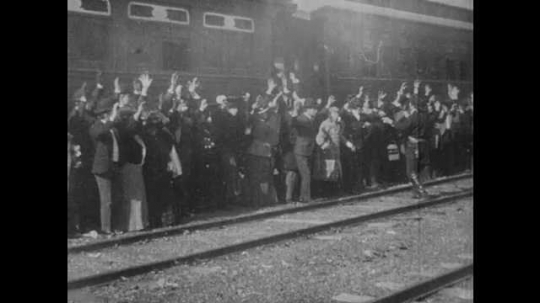 1900s: UNITED STATES: train passengers hold arms in air. Passengers at gunpoint on tracks