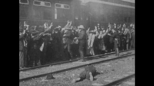 1900s: UNITED STATES: robbers steal from train passengers. Robbers fire guns. Passengers run to injured man