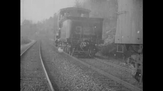1900s: UNITED STATES: train robbers run to engine carriage. Train on tracks