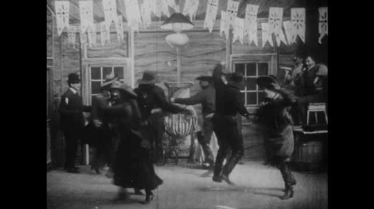 1900s: UNITED STATES: ladies and men dance at ball. Square dancing