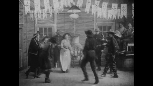 1900s: UNITED STATES: couples square dance. Band plays. Men ride horses through woods. Men chase robbers. Men shoot guns. Man jumps from horse. Man on ground
