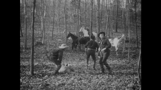 1900s: UNITED STATES: robbers tip out swag from bag. Men surrounded in woods. Men shoot at robbers. Horses stand near robbers in gun fire