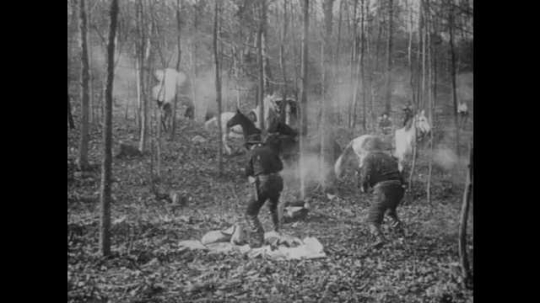 1900s: UNITED STATES: men shoot at robbers in woods. Men shoot robbers. Man fires gun at camera