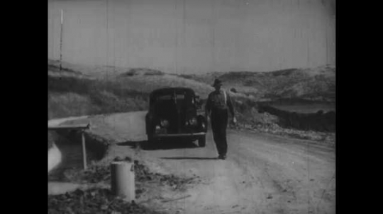 1930s: Parked car on road next to irrigation canal, man next to car, farmer with shovel walks towards him. Water flows in irrigation canal. Men go to canal, man turns pole inside water, pulls it up.