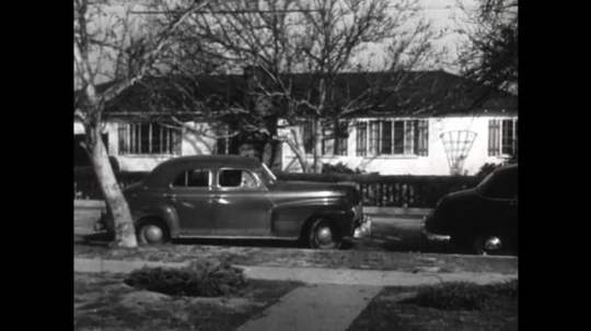 United States: 1950s: car drives from house. Car pulls out in front of traffic. Girl shrugs. Man comes through door of house. Man and girl talk.