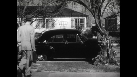 United States: 1950s: man walks lady to car. Man gets into car. Lady gets into car. Car drives away from house.
