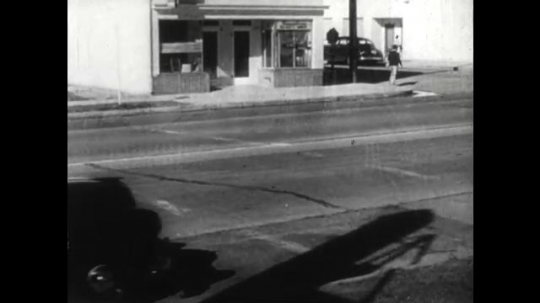 United States: 1950s: car pulls over at side of street. Lady gets out of car. Lady closes car door and says goodbye. Car drives off. Car nearly gets hit by traffic.