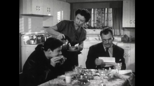 United States: 1950s: boy eats in hurry at table. Man talks to boy. Lady pours drink. Boy drinks from glass. Boy kisses mother and leaves.