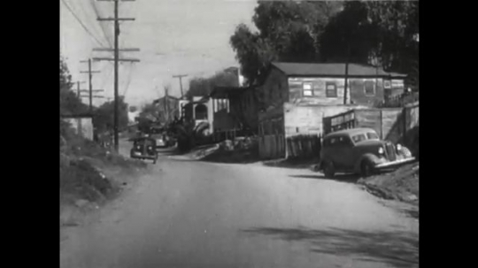 United States: 1950s: view along street. Truck parked by house.