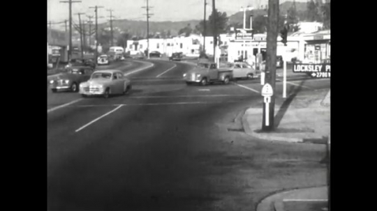 United States: 1950s: cars drive on busy road. Two way traffic on road. Cars drive near box junction.