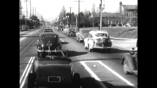 United States: 1950s: cars drive along road. Traffic lights change colour. Cars stop at traffic lights.