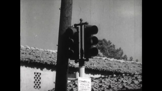 United States: 1950s: traffic light changes colour. Car pulls out from road. Lady looks at papers and misses traffic light. Driver looks at lady. Man beeps horn.