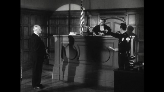 United States: 1950s: police officer passes paper to judge. Jude talks to man.