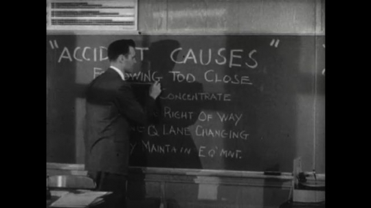 United States: 1950s: man underlines words on board. Accident causes notes on blackboard. Man tests girl