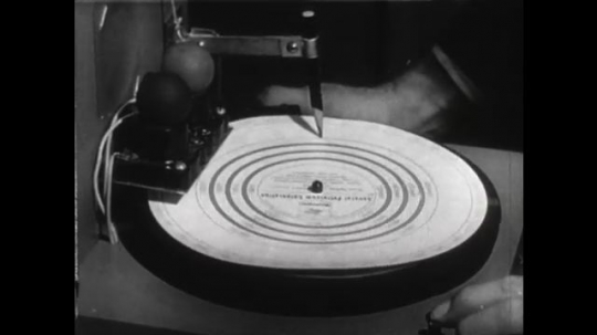 United States: 1950s: pencil makes mark on rotating paper. Finger points at paper disc of reaction times.