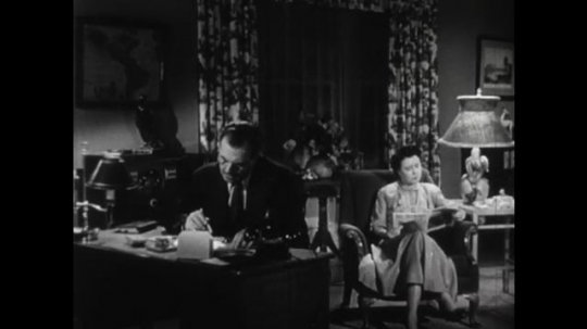 United States: 1950s: man sits at table in house. Lady reads paper. Lady returns home. Lady takes off jacket. Lady in house with children.