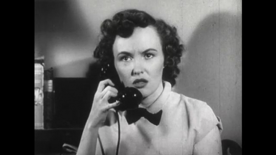 United States: 1950s: lady speaks on telephone. Close up of lady's face. Lady receives bad news. Fire and flames around car crash.