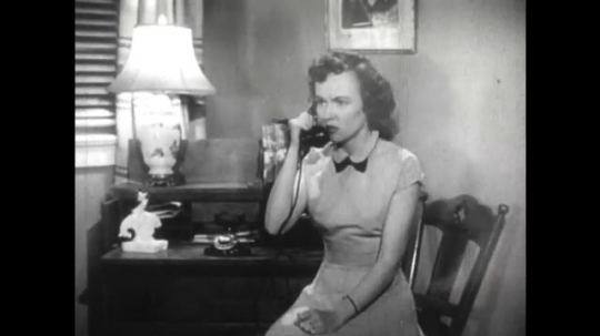 United States: 1950s: lady speaks on telephone. Lady puts down phone. Lady receives bad news by phone.