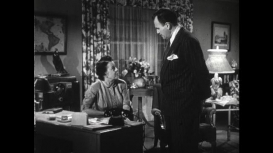United States: 1950s: lady and man talk in room of house. Close up of man