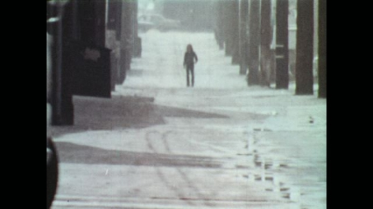UNITED STATES: 1970s: guy walks down hill in city.