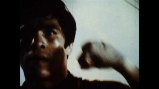 UNITED STATES: 1970s: young man boxing indoors. Guy watches boxing practice