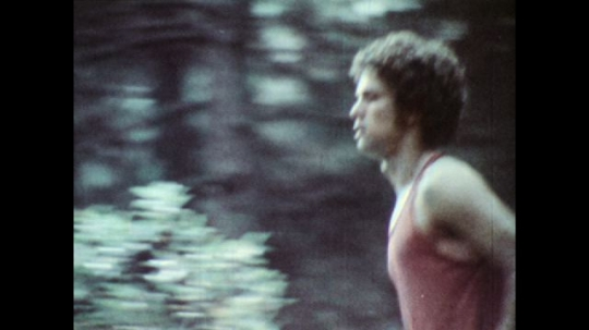 UNITED STATES: 1970s: man runs in woods. Close up of runner's feet.