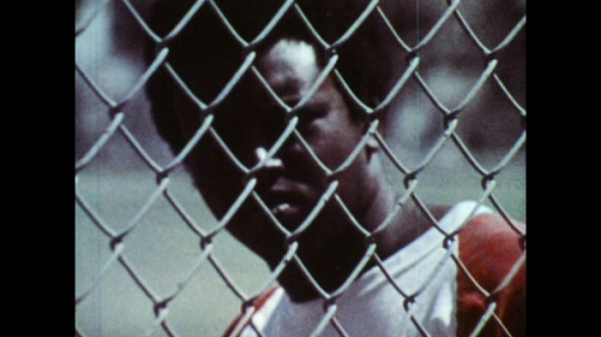 UNITED STATES: 1970s: Guy watches basketball players through fence. Flies on dead fish
